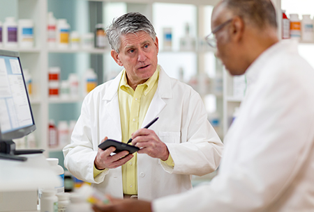 Two Doctors discussing, bottles in background