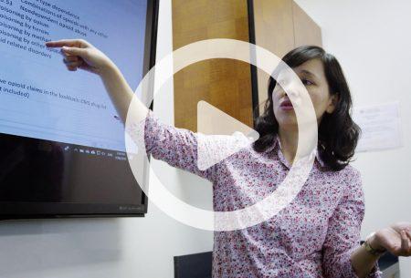 Dr. Jenny Wei analyzes data on a TV screen