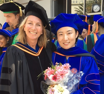 Almut winterstein and student posed for graduation image